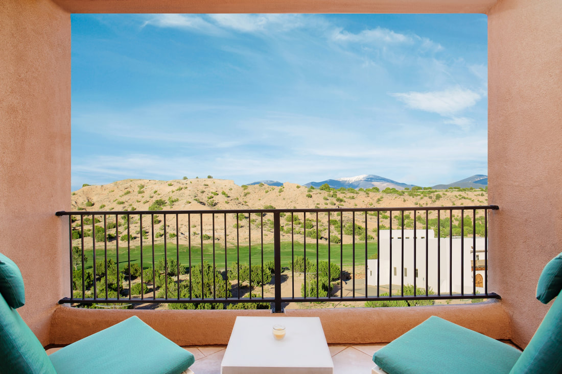 Chairs on balcony overlooking golf course and desert
